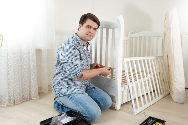 Young Handyman Sitting On Floor At Empty Room And Assembling New Furniture