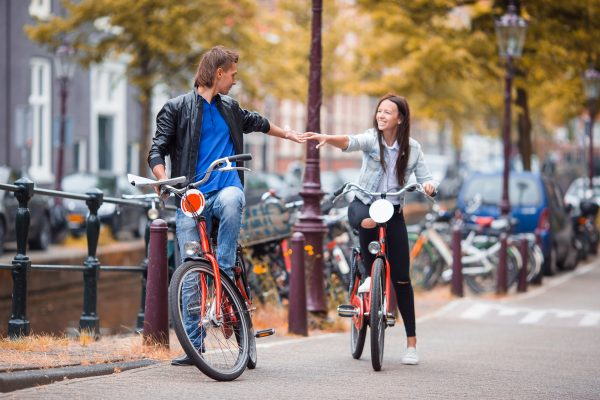 Young Happy Ouple On Bikes In Old Streets In Amsterdam