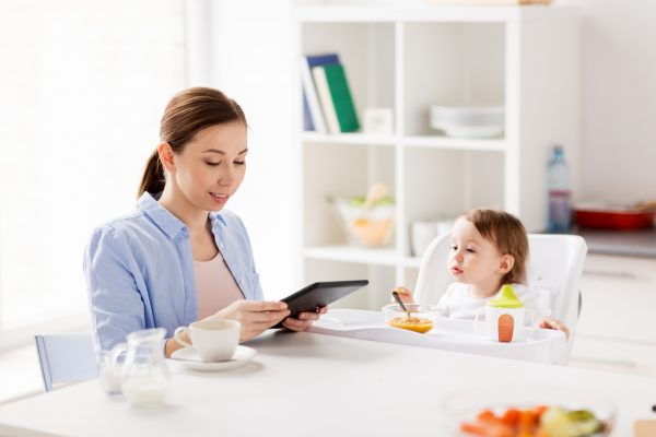 Family, Food, Eating, Breakfast And People Concept - Happy Mother With Tablet Pc Computer And Little Baby Sitting In Highchair At Home Kitchen
