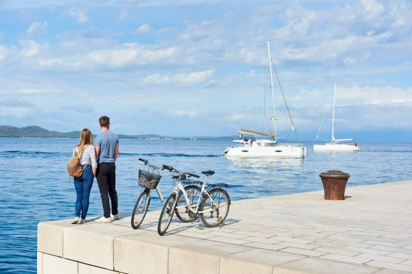 Back View Of Tourist Couple, Man And Woman With Backpack Standing At Bicycles On High Paved Stone Sidewalk Watching Floating Cruise Yachts In Clear Blue Sea Water On Sunny Day. Active Holiday Concept.